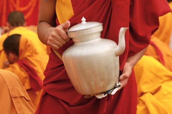 Tibetan tea teapot in the hands of a monk in Nepal