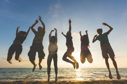 Multiracial group of people jumping at beach