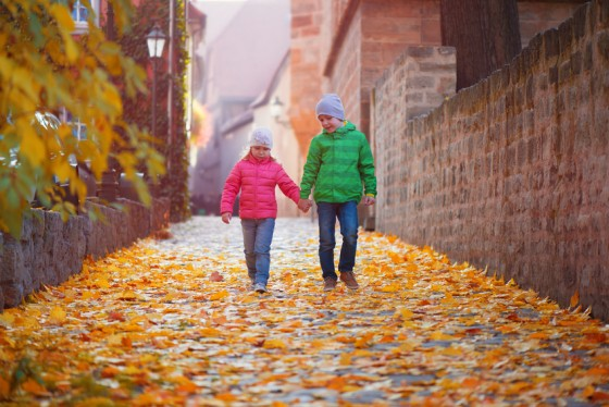 Two cute children walking in autumn town