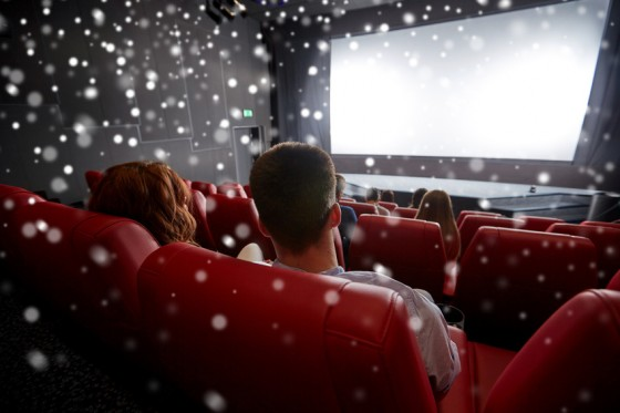 cinema, entertainment, leisure and people concept - couple watching movie in theater from back over snowflakes